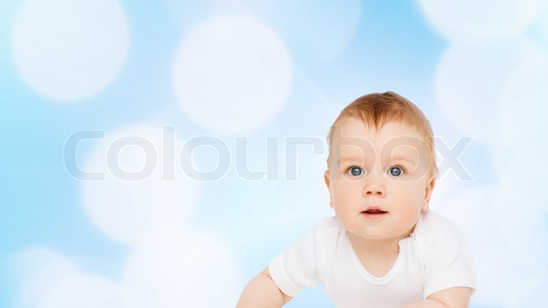 Child and toddler concept - smiling baby lying on floor and looking up, stock photo