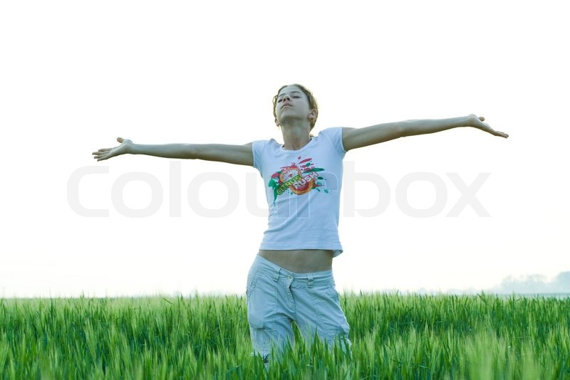 teenage girl standing with arms outstretched in the field stock