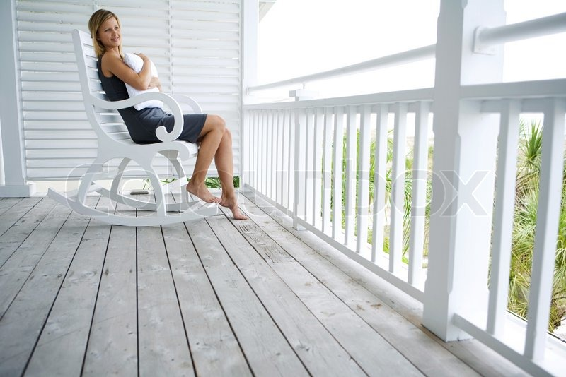 Contemplative Woman Sitting In Rocking Chair On Porch And