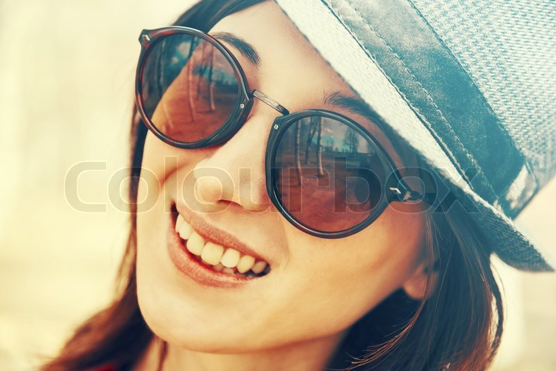Stock image of 'Portrait of happy young woman in sunglasses and hat, hipster style. Image with vintage filter'