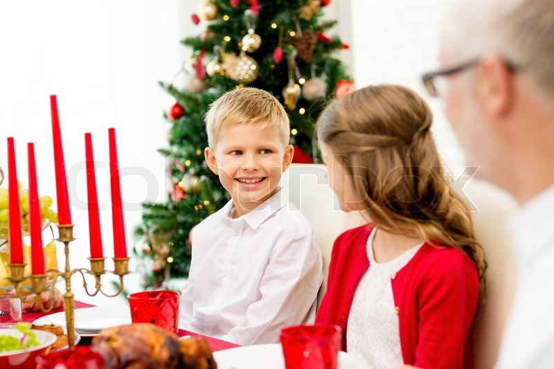 Family, holidays, generation, christmas and people concept - smiling family having dinner at home, stock photo