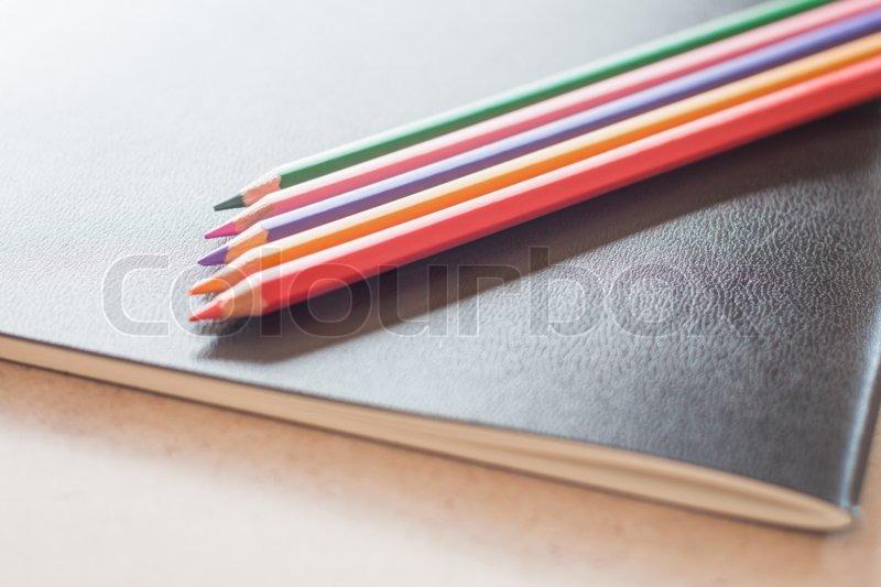 Closeup color pencils on black notebook, stock photo, stock photo