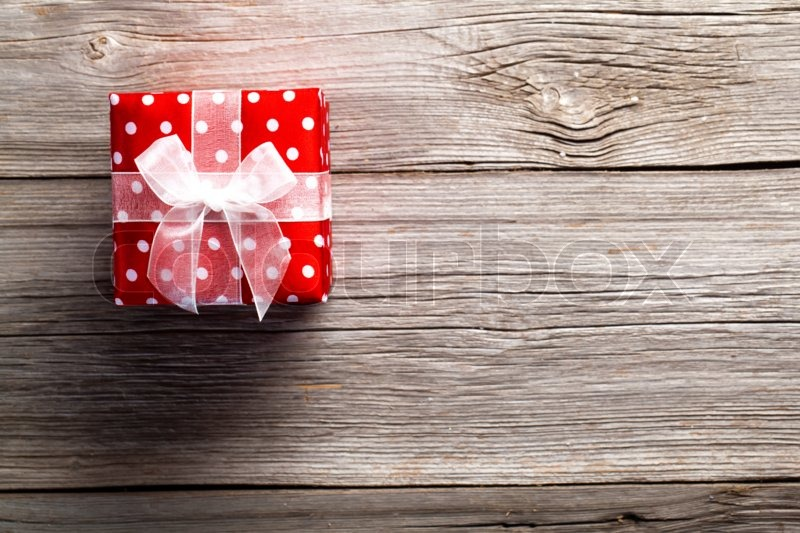 Red gift box, polka dots, on wood background, stock photo