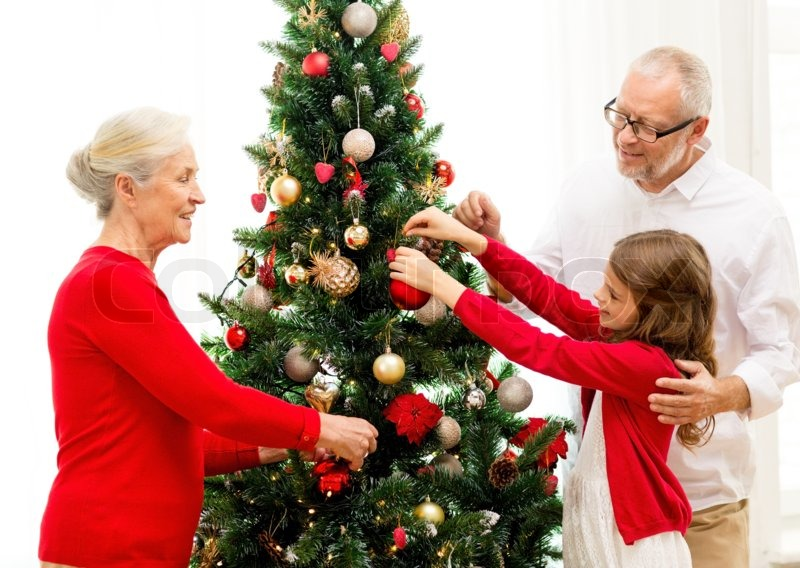Family, holidays, generation and people concept - smiling family decorating christmas tree at home, stock photo