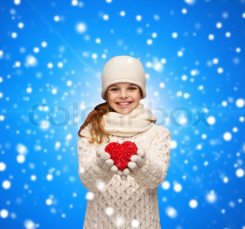 Christmas, holidays, childhood, presents and people concept - dreaming girl in winter clothes with red heart over blue snowing background, stock photo