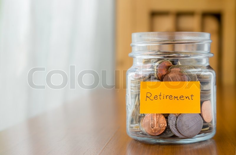 World coins in glass savings jar with retirement plan label, stock photo