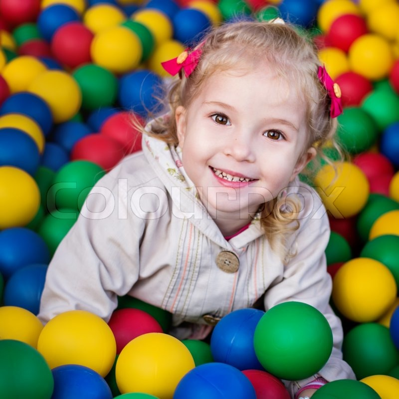 Happy little girl playing on colorful balls playground , stock photo