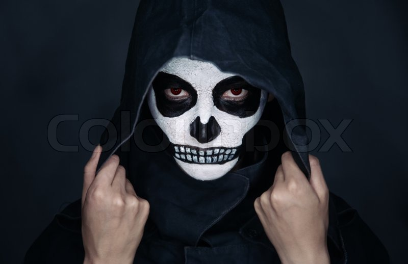 woman with skull makeup in hood looks at camera halloween face art stock photo colourbox