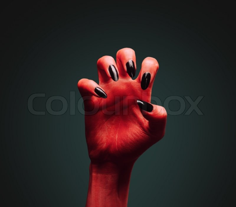 scary red devil hand on dark background halloween or horror theme