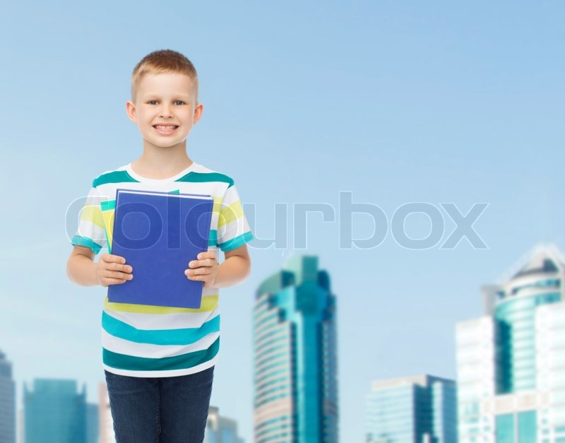 Education, childhood and school concept - smiling little student boy with blue book over city background, stock photo