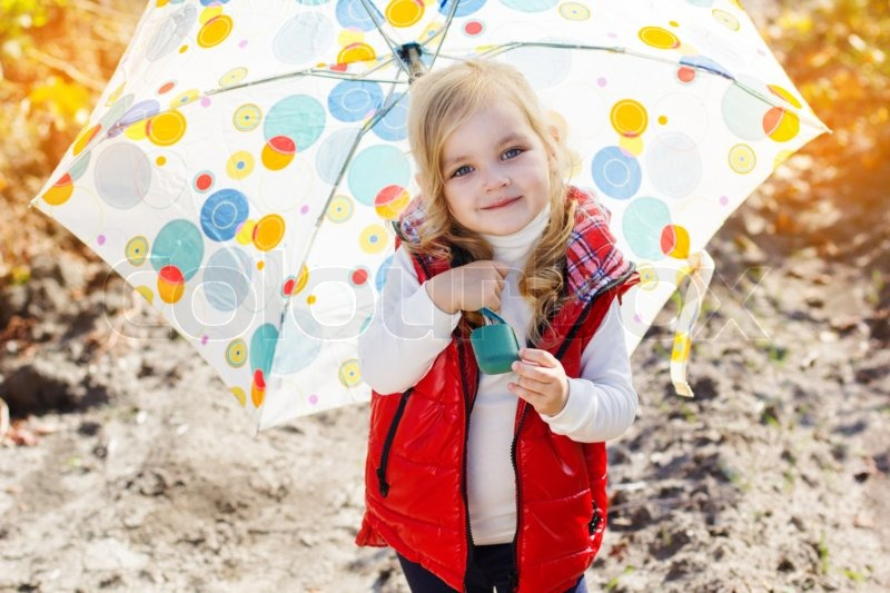 Smiling little girl with umbrella is wearing warm red vest and boots walking on the vineyard, stock photo