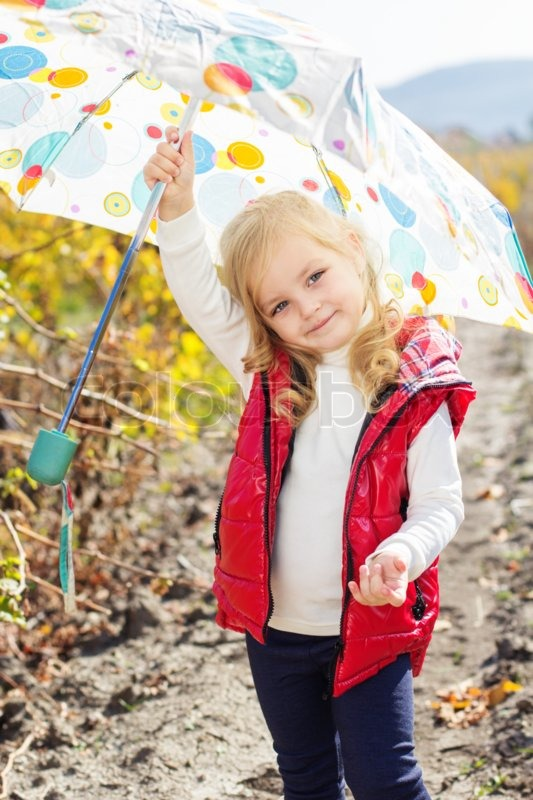 Smiling little girl with umbrella is wearing red vest and boots walking on the vineyard, stock photo