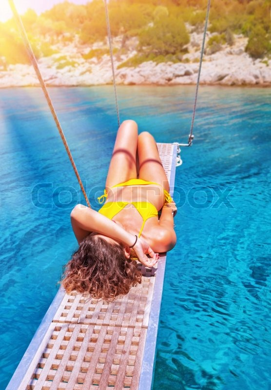 Stock image of 'Sexy woman tanning on sailboat, female relaxing above transparent blue sea, girl enjoying bright sun light, active lifestyle, happy summer vacation'