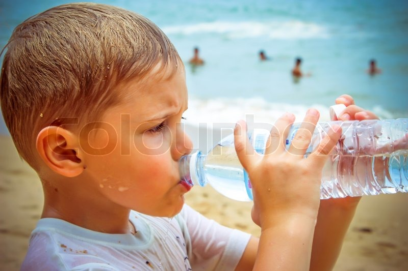 Little boy drinking water on the beach after hard swimming lesson, stock photo