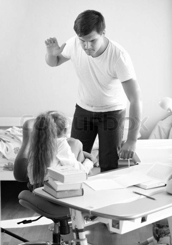 Black and white shot of angry father hitting intimidated daughter, stock photo