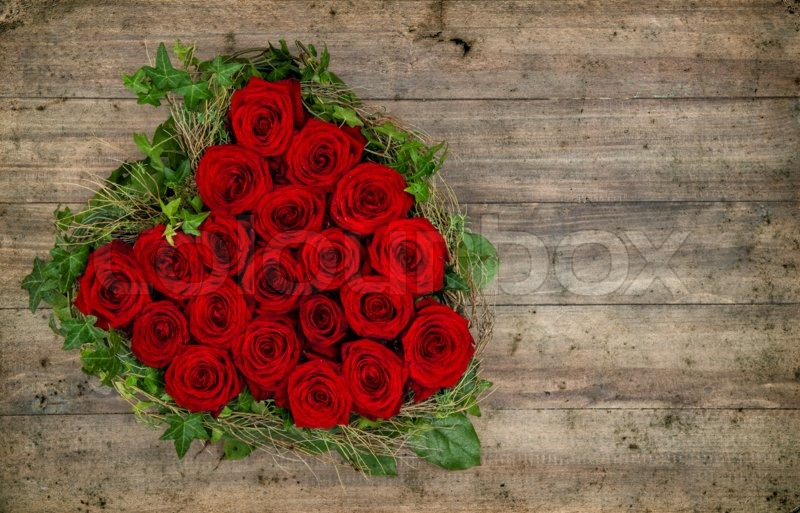 Heart shaped red roses bouquet on rustic wooden background ...