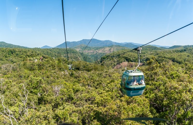 Cable car with tourists suspended travels high over tropical rain forest roof at Kuranda Cairns, stock photo