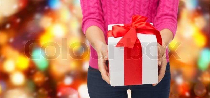 Christmas, holidays and people concept - close up of woman in pink sweater holding gift box over red lights background, stock photo