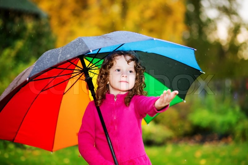 Little Girl Under Rainbow Umbrella Held Out Her Hand And