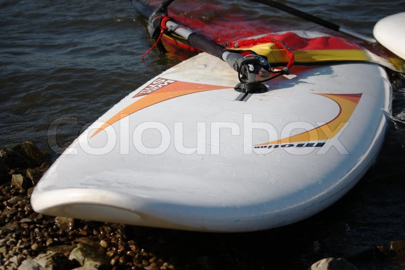 Windsurfing board on a stone covered beach, stock photo