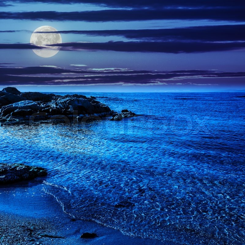 Calm Sea With Some Wave On Sandy Beach Stones At Night