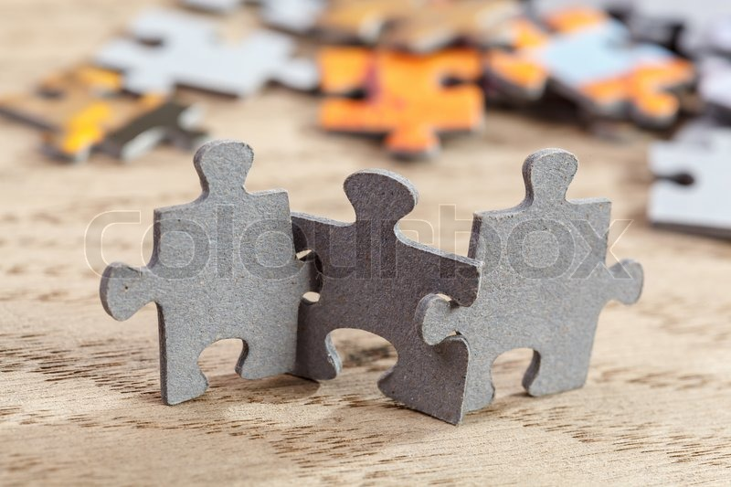 Concept of teamwork: Three jigsaw puzzle pieces on a table joint together. Shallow depth of field, stock photo