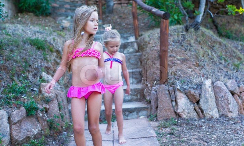 Two adorable little girls in swimsuits during the summer holidays, stock photo