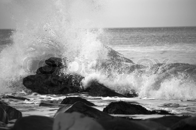 Waves crashing over rocks on the sea shore in black and white, stock photo