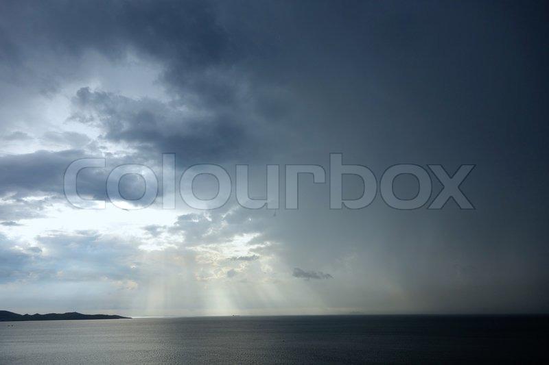 Rainy sky with sun beams, stock photo