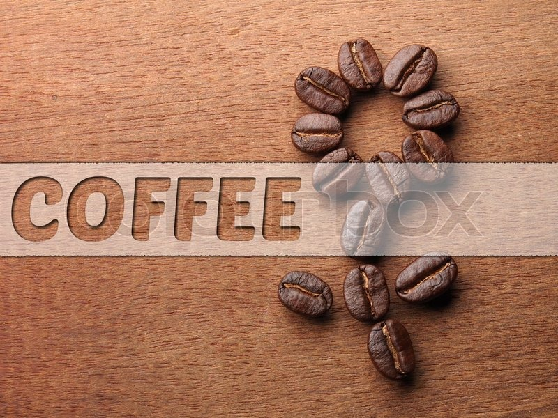 Coffee crop beans on wood texture background, stock photo