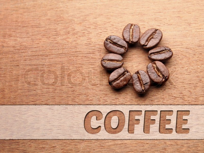 Coffee crop beans with text paper on wood texture, stock photo