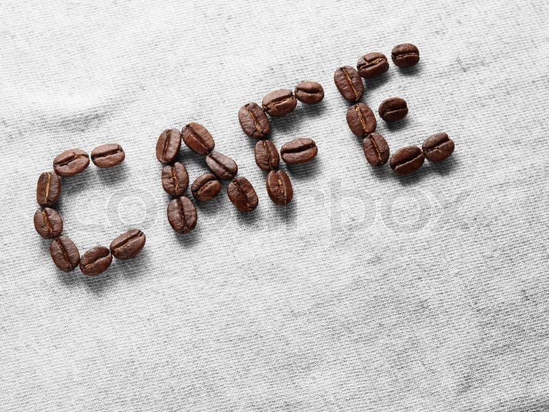 Coffee crop beans on fabric textile texture background, stock photo