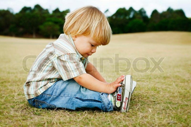 Stock image of 'Little boy sitting on grass'