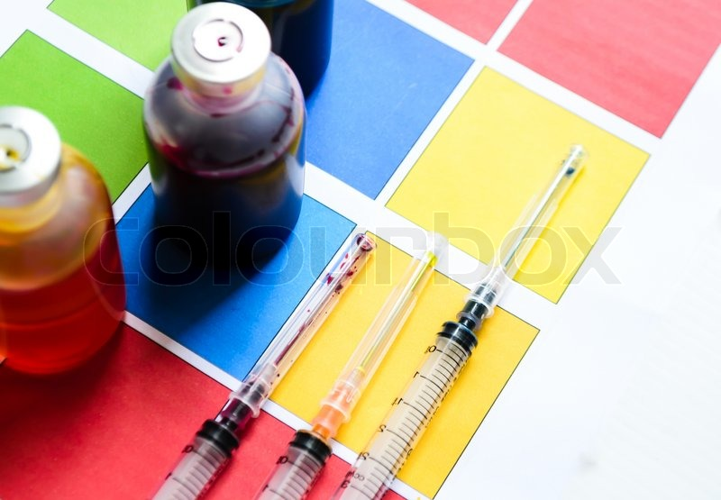 Bottle of ink printer has three colors. Colors is red, yellow and blue with syringe on colored paper, stock photo