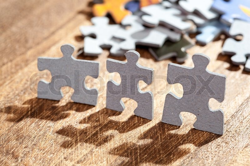 Closeup of three jigsaw puzzle pieces on a table lit by back light. Shallow depth of field, stock photo