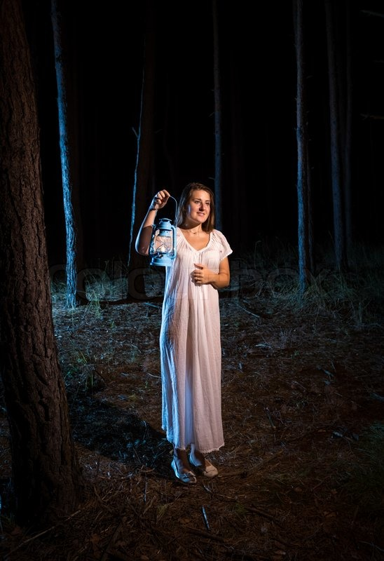 Lonely Young Woman In Nightgown Walking In Forest At Night