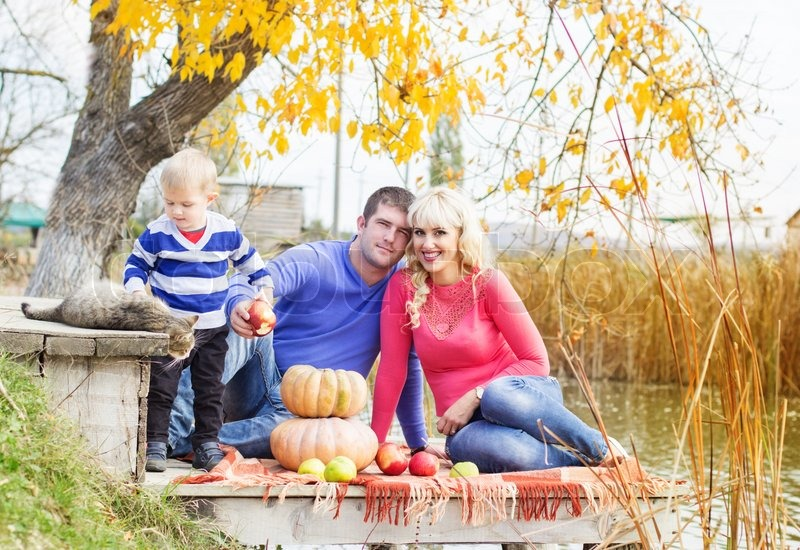 Young pretty happy family son,mother and father with pumpkins near lake with cat, autumn time, stock photo
