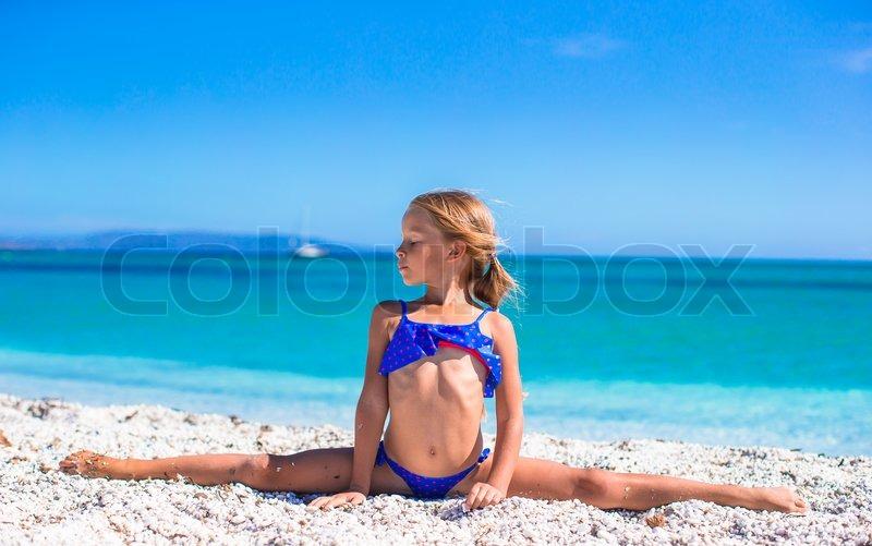 cute little girl having fun making leg split and enjoying vacation