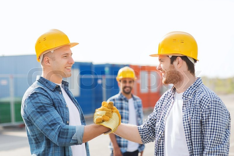 Business building teamwork gesture and people concept group of business building teamwork gesture and people concept group of smiling builders in hardhats greeting each other with handshake outdoors stock photo m4hsunfo