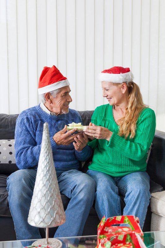 Senior couple give gift box christmas present, sitting on sofa smile, stock photo
