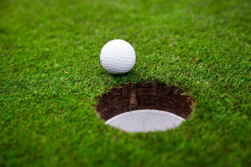 Golf ball on green meadow. golf ball on lip of cup, stock photo