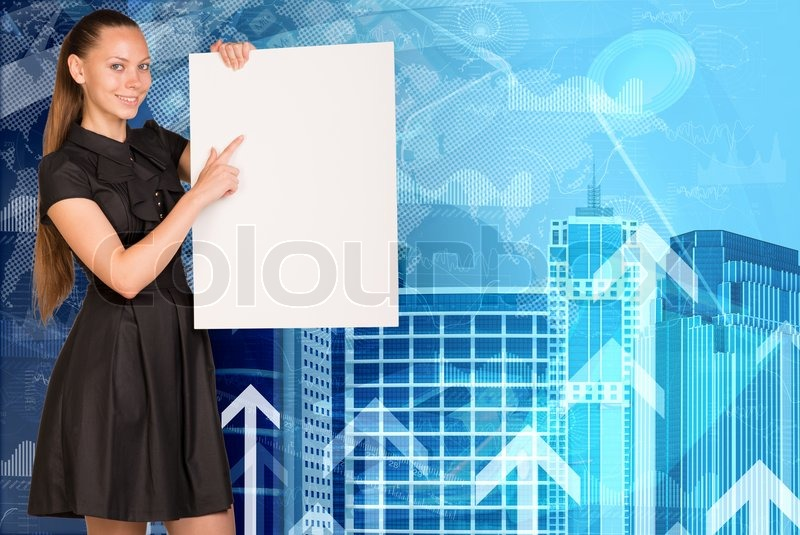 Beautiful businesswoman in dress smiling and holding empty paper sheet. Buildings and arrows as backdrop, stock photo
