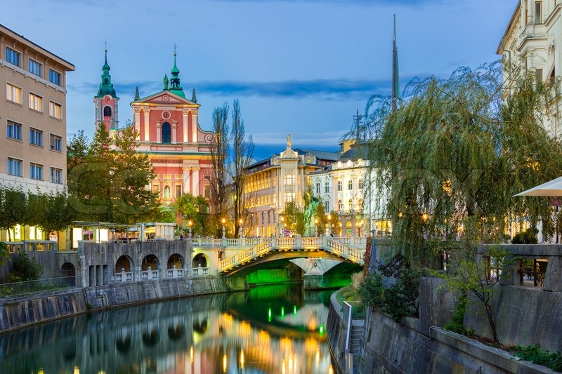 Romantic medieval Ljubljana\'s city center, capital of Slovenia, Europe. Night life on the banks of river Ljubljanica where many bars and restaurants take place. Franciscan Church in background, stock photo