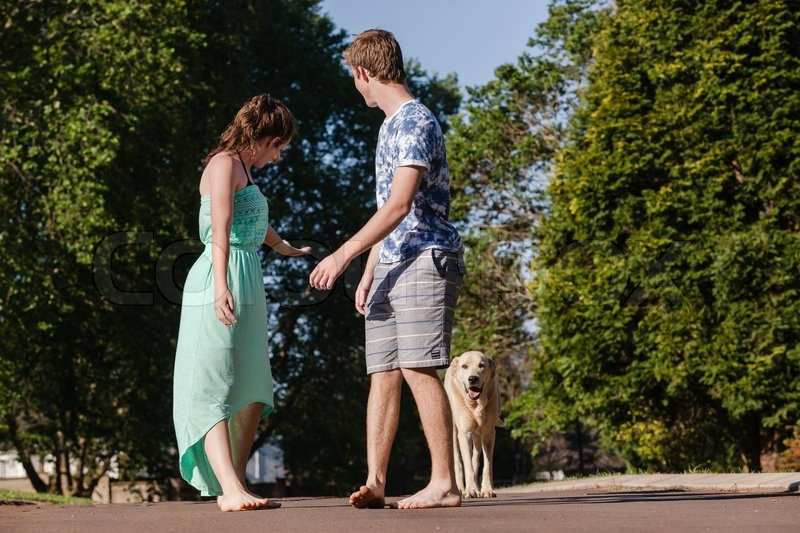 Teenagers girls boy hangout with dogs summers day home talk laugh playtime relaxing, stock photo
