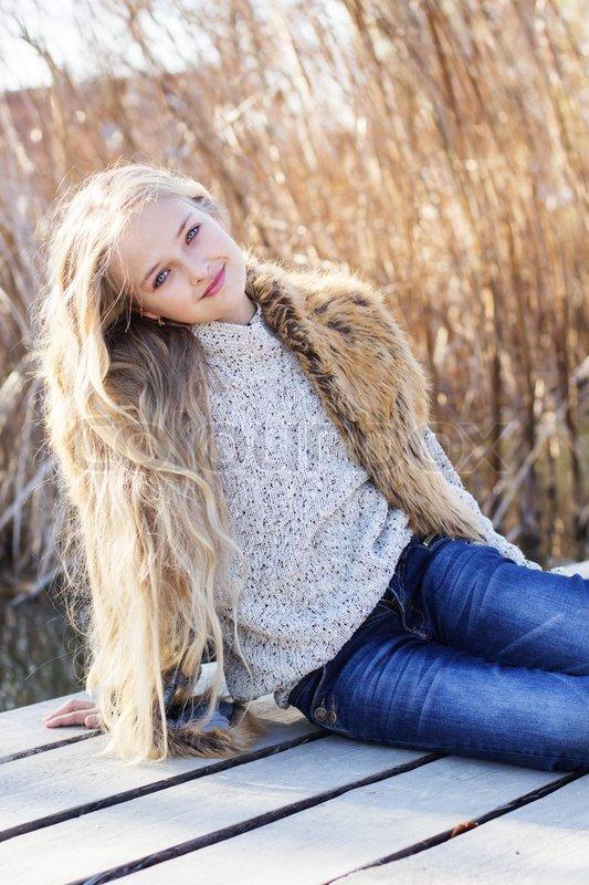Little Cute Girl Outdoors Is Wearing Fashion Fur Vest In