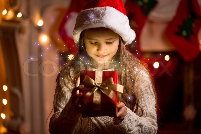 Little cute girl looking inside of glowing Christmas present box, stock photo