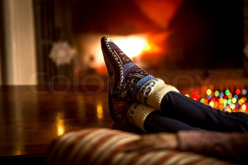 Closeup portrait of feet at woolen socks warming at fireplace in ...