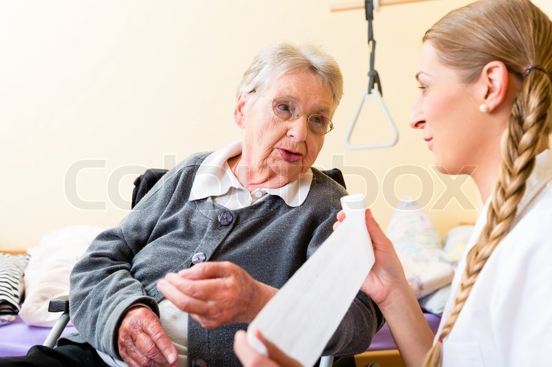 Nurse taking care of senior woman in retirement home bandaging a wound, stock photo