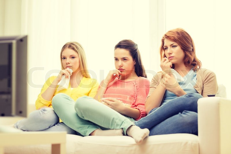 Home, technology and friendship concept - three sad teenage girl watching tv at home and eating popcorn, stock photo