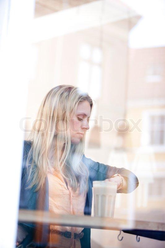 03f0667464a2 En kvinde på en café der drikker kaffe ...